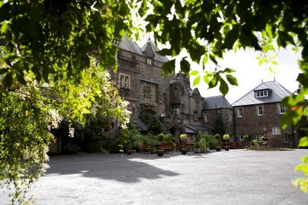 View of Craig y Nos Courtyard through arch of trees from theatre gardens, Swansea Valley, Wales