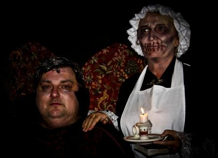 Swansea hen parties organiser Steve Graham in Fright Night costume as Dracula alongside 'Muted Maid' character holding a candle
