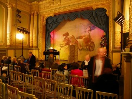 A musical concert at Craig y Nos Opera House, Swansea, Wales, grand piano on stage, Patti on chariot curtain